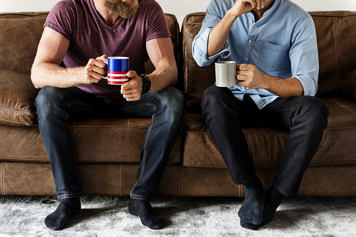 two men wearing casual clothes sitting on a brown couch drinking coffee from mugs and talking