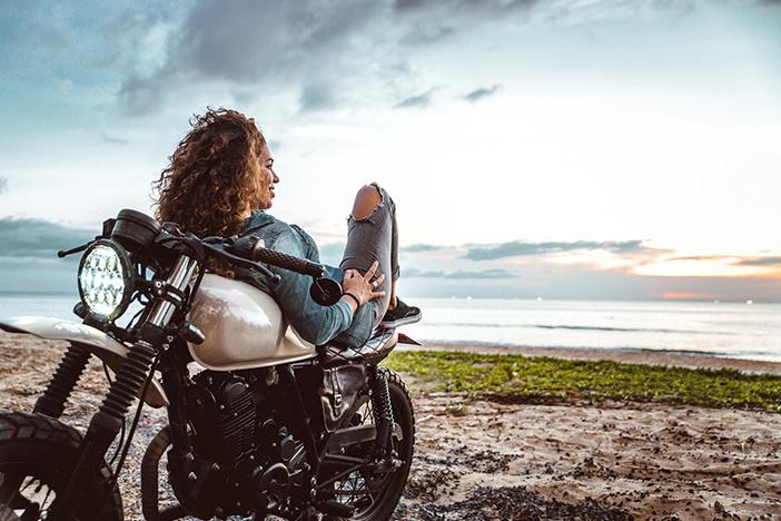 Beautiful girl having fun driving her motorcycle, enjoying the sunset on the beach