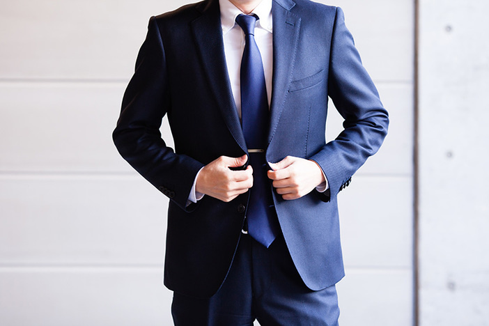 torso of caucasian man wearing navy blue suit and tie