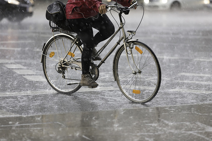 closeup of lower half of a person riding a bicycle in heavy rain on city street