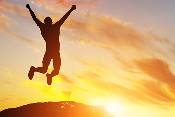 man on mountain peak jumps up victoriously with arms extended overhead during sunrise or sunset