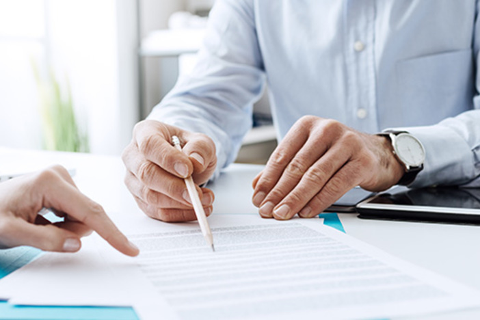 closeup of two people going over business documents fanned out on desk and pointing to line items with finger and pencil
