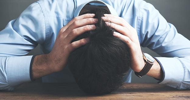 man in despair head on hand sitting in table