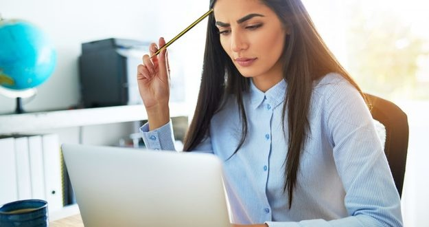 Young Asian businesswoman frowning with concern as she tries to understand something she is reading on her laptop computer scratching her head with her pencil in perplexity
