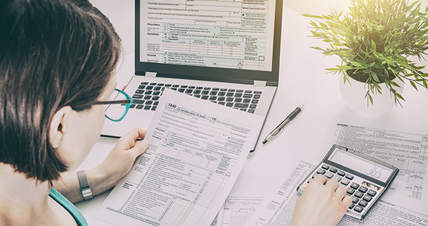 woman at desk with paper tax forms, tax form on lap screen, calculator, pen, plant