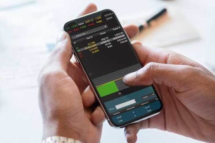 closeup of man holding smart phone checking stocks