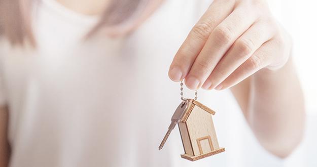 Female hand holding key house shaped keychain.