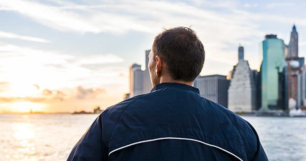 man looking out over river at cityscape and sunset