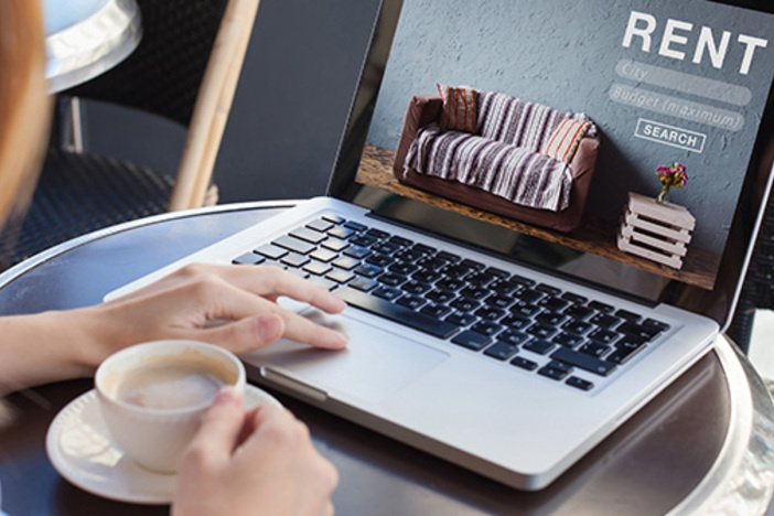 woman using internet website for rental apartments, houses