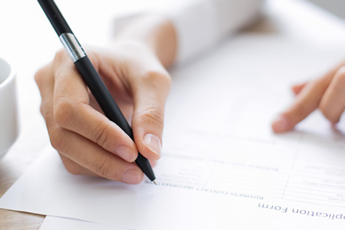 Cropped view of woman holding pen and filling out application form at table with focus on hand with pen