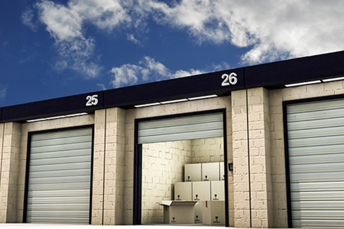 self-storage facility with garage door open and packed boxes stacked inside