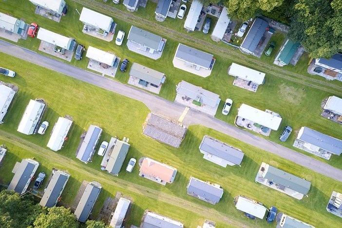 Caravan site park aerial view illuminated by summer sun