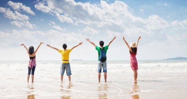 four people on beach in colorful clothing facing ocean with arms in air