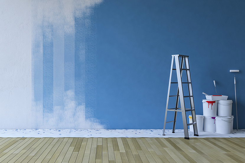 painting blue wall in an empty room. ladder and paiting tools placed on timber floor.