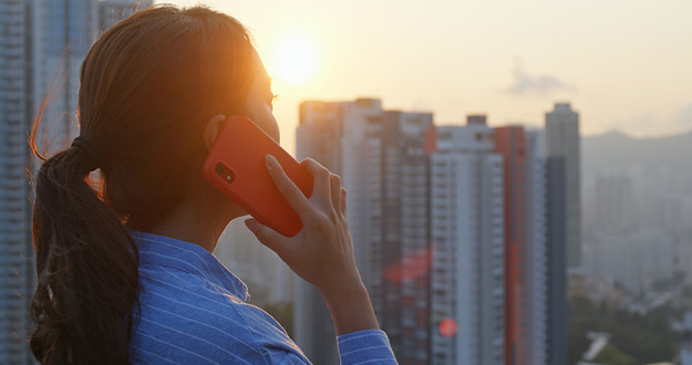Woman talking on cellphone with the city background under sunlight