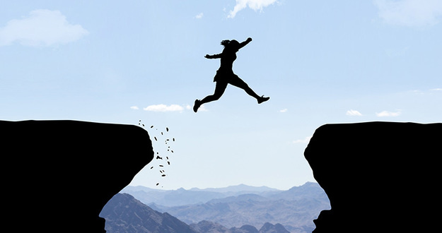 silhouette of woman leaping off one cliff aiming to land on another several feet away, conveying leap of faith