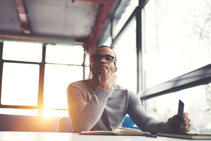 Pensive afro american handsome professional writer of popular articles in blog dressed in trendy outfit and glasses thinking over new story proofreading his script from notebook sitting in cafe