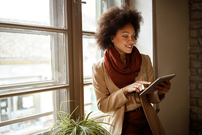Young Afro-American woman near window on workplace taking information from ipad