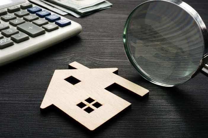 Property assessment. Wooden house with magnifier and calculator.