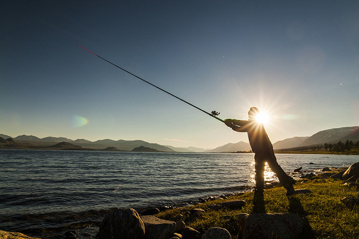 Silhouette of a fisherman at sunset. Fishing on mountain lake
