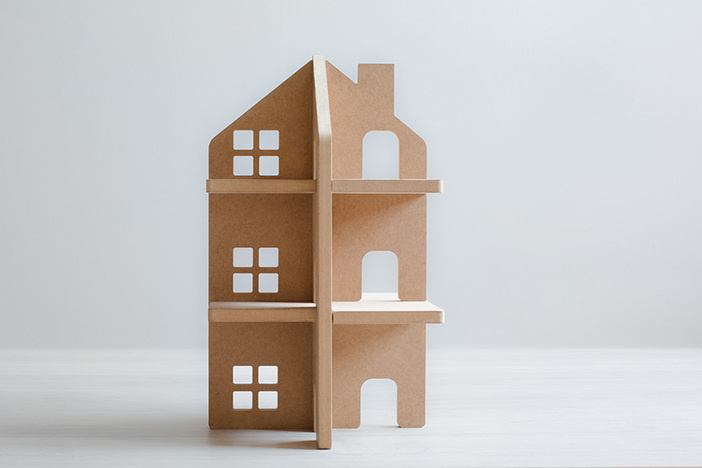 wooden model of multifamily property on gray background