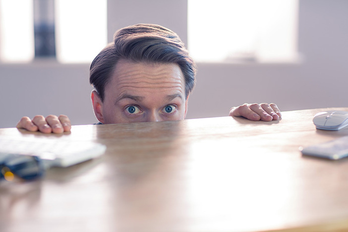 Nervous businessman peeking over desks