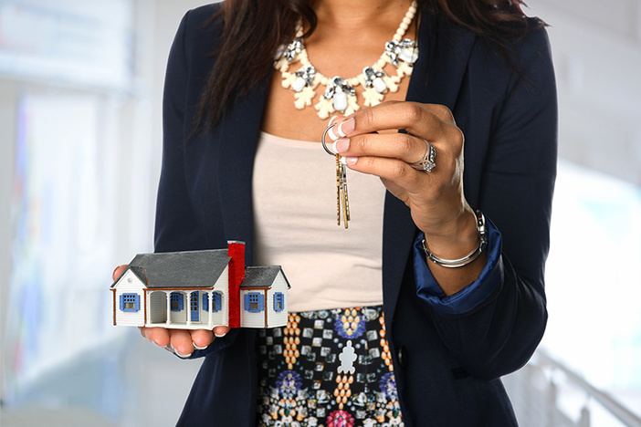 Female real estate agent holding house and keys