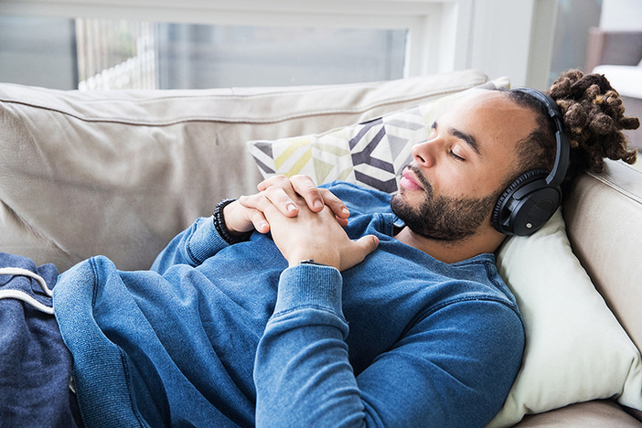 african american young man lying on couch listening to headphones