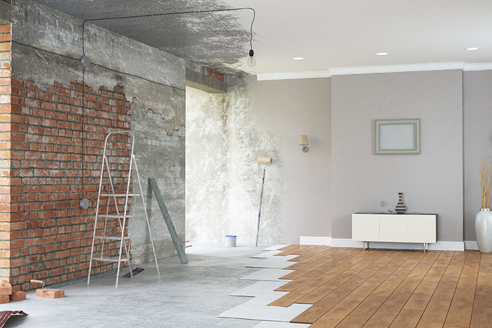renovation interior with vinyl plank flooring and faux brick wall and gray paint