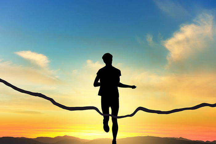 silhouette of human figure running through ribbon at finish line set against vividly colored sunset and foothill backdrop