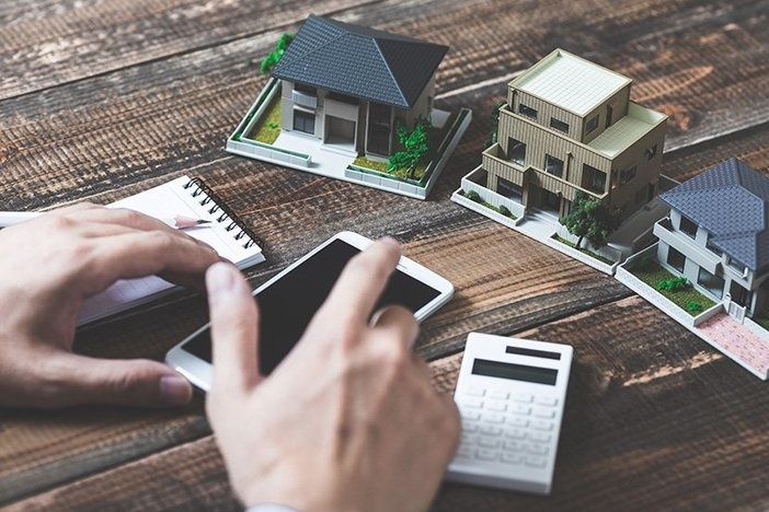 real estate investment small plastic property models on wooden surface with notepad, calculator, smartphone, male hands in view