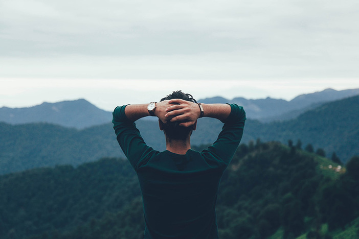 man facing away from camera looking out at mountain range