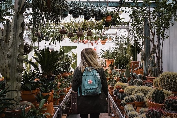 blond-haired women with backpack walking down aisle of plant nursery