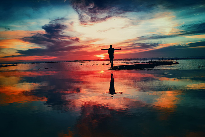 colorful sunset backdrop with arms open as if embracing