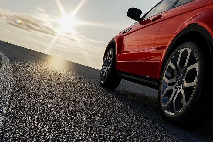 brand new red sedan driving on dark pavement with sunbeam ahead in partly cloudy sky