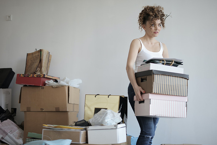 woman carrying stack of boxes with more boxes stacked in background