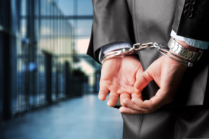 Businessman in suit in handcuffs