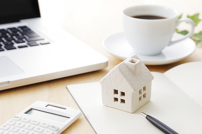 wooden model of house on desk with coffee cup, calculator, laptop