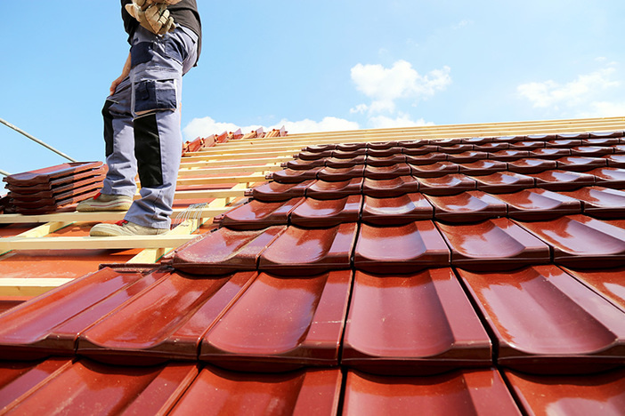 worker standing on roof installing new tiles