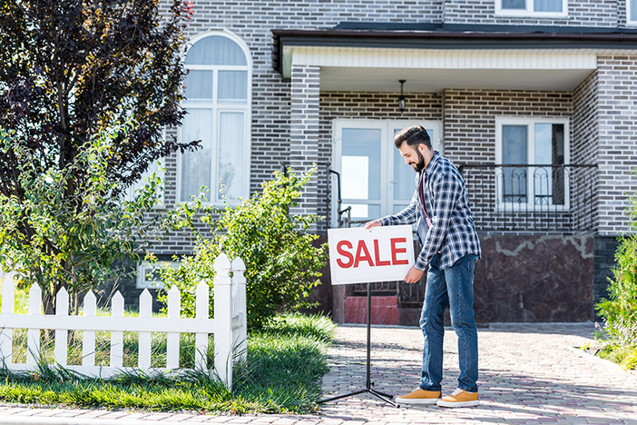 young man placing sale sign in front of his house