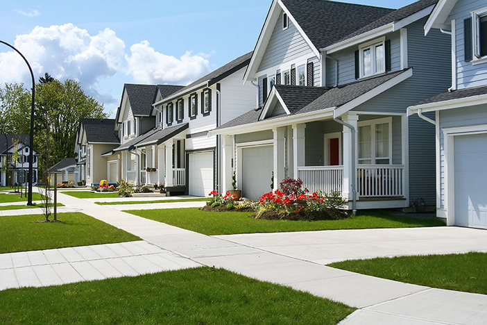 medium to large sized homes on neighborhood street with well manicured lawns