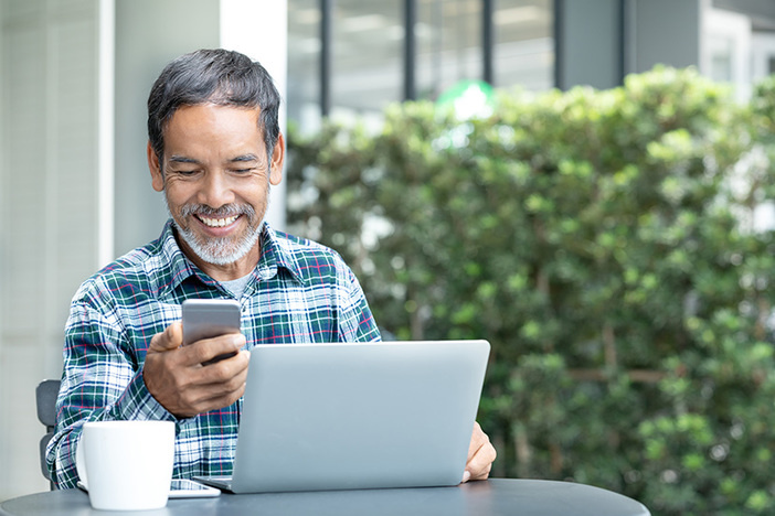 Smiling happy mature man with white stylish short beard using smartphone gadget serving internet at coffee shop cafe outdoor. Laughing old man using social media network technology feeling excited.