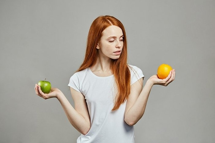 red haired caucasian woman comparing apples and oranges.