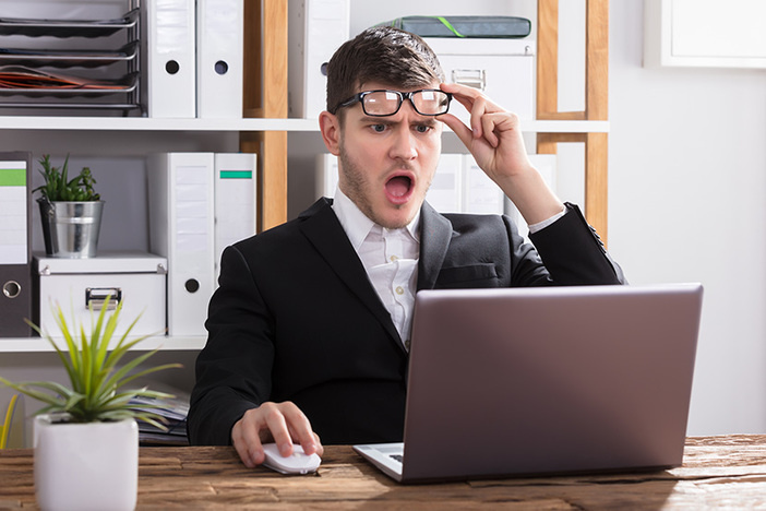Shocked Young Businessman Looking At Laptop In Office