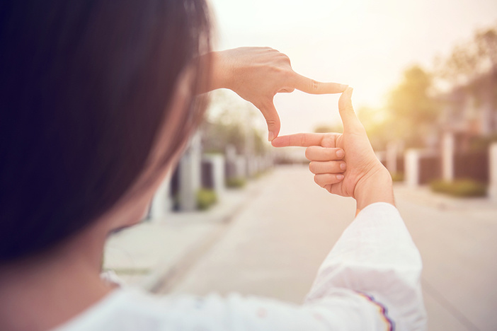 Close up of woman hands making frame gesture with sunlight outdoors