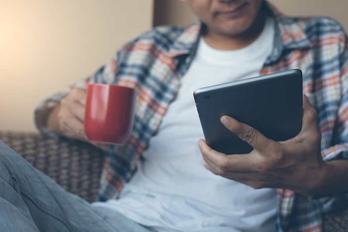 Casual man or hipster drinking coffee and looking at digital tablet screen near the window at home with morning light. Man checking internet application on digital tablet computer, modern lifestyle concept, flare light