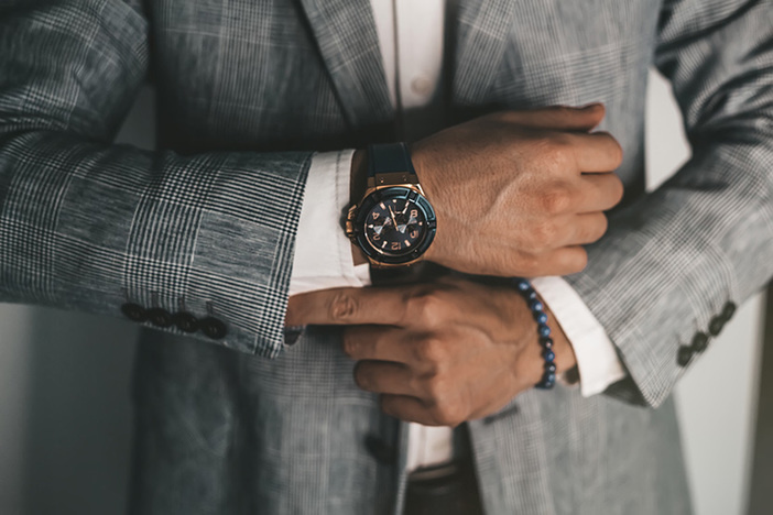 Closeup fashion image of luxury watch worn by male in gray suit