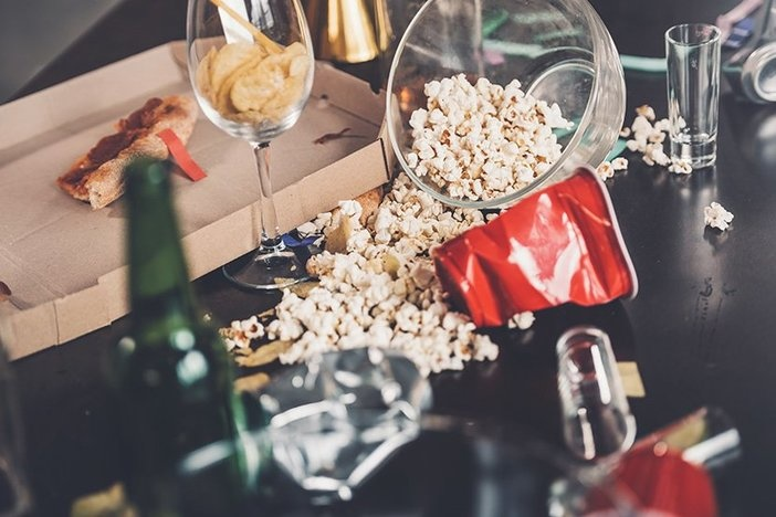 Close-up view of popcorn, glasses and trash on messy table after party