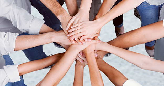 closeup of hands piled on top of one another indicating teamwork