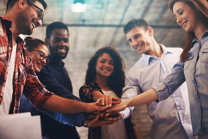 racially diverse group of young people with hands stacked on top of one another standing in semi-circle